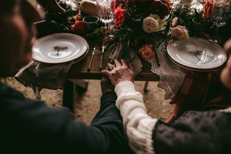Couple holding hands at intimate tablescape