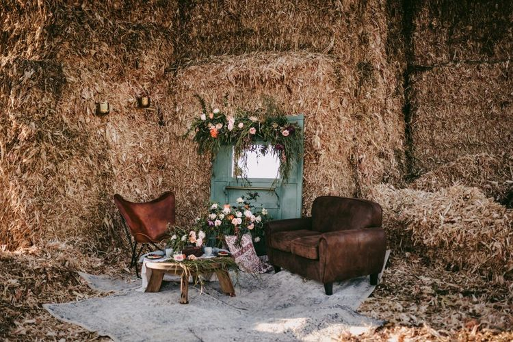rustic seating area with leather chairs, flowers and hay bales
