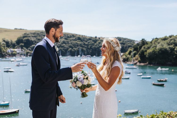 Bride in Sophia Tolli Galene Wedding Dress and Groom in Navy Blue Ted Baker Suit Toasting by the Dock