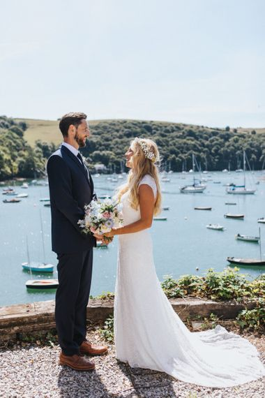 Bride in Sophia Tolli Galene Wedding Dress and Groom in Navy Blue Ted Baker Suit Embracing by The Marina