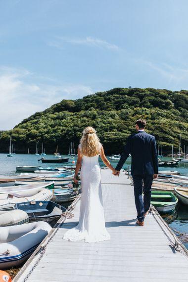 Bride in Sophia Tolli Galene Wedding Dress and Groom in Navy Blue Ted Baker Suit Walking on the Dock