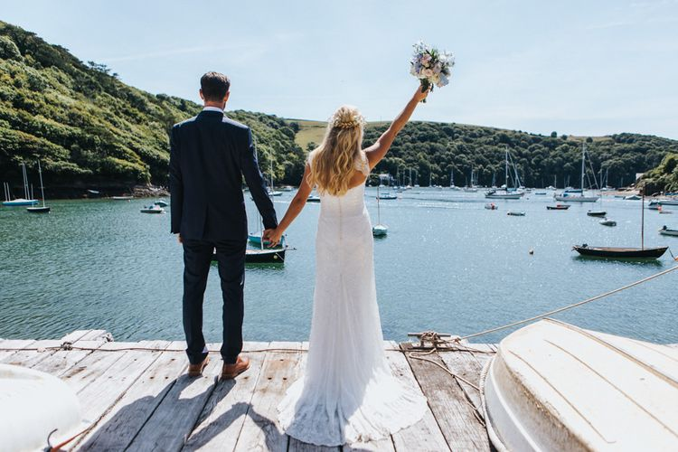 Bride in Sophia Tolli Galene Wedding Dress and Groom in Navy Blue Ted Baker Suit Celebrating by by the Dock