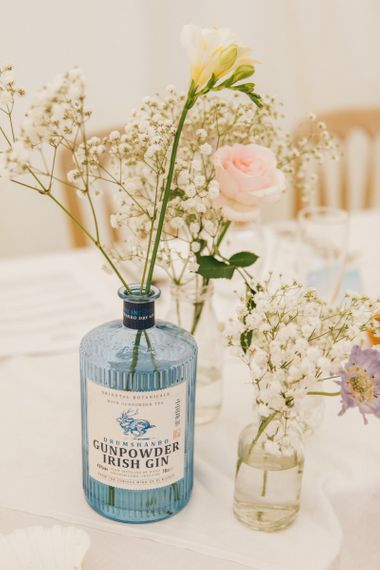 Gin Bottles Filled with Flower Stems as Centrepieces