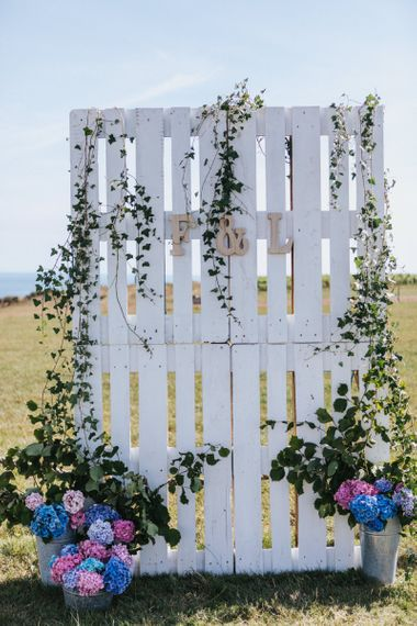 Wooden Pallet Backdrop Covered with Ivy and Buckets Filled with Pink and Blue Hydrangeas