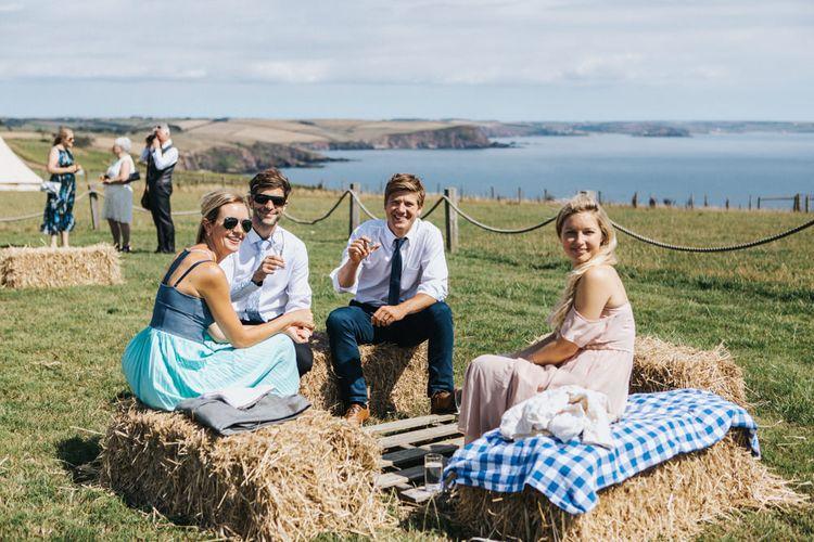 Wedding Guests Sitting on Hay Bales