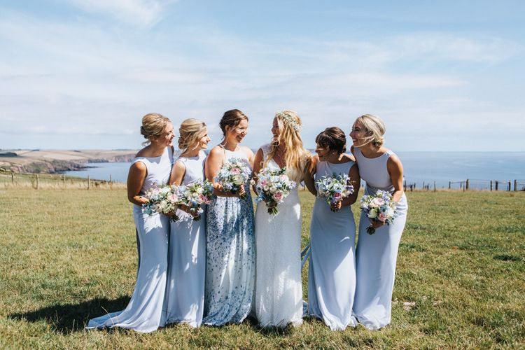 Bridal Party Portrait with Maid of Honour in Floral Dress, Bridesmaids in Pale Blue Dresses and Bride in Sophia Tolli Wedding Dress