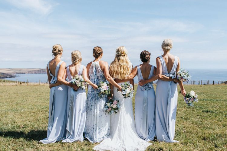 Bridal Party Portrait with Maid of Honour in Halterneck Floral Dress, Bridesmaids in Pale Blue Dresses with Bow Back and Bride in Sophia Tolli Wedding Dress