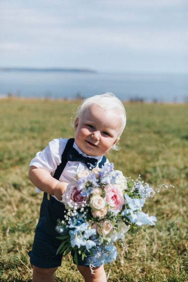 Cute Page Boy in Bow Tie and Braces Holding a Pastel Pink and Blue Wedding Bouquet