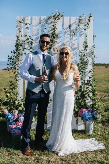 Bride in Sophia Tolli Wedding Dress and Groom in Grey Waistcoat Posing in Front of Palette Backdrop