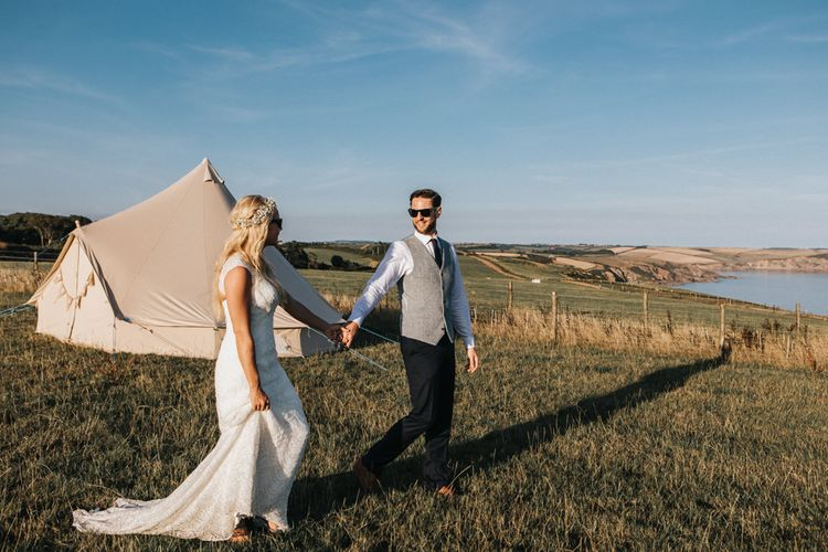 Bride in Sophia Tolli Wedding Dress and Groom in Grey Waistcoat Walking on Cliff Where their Bell Tent is Pitched