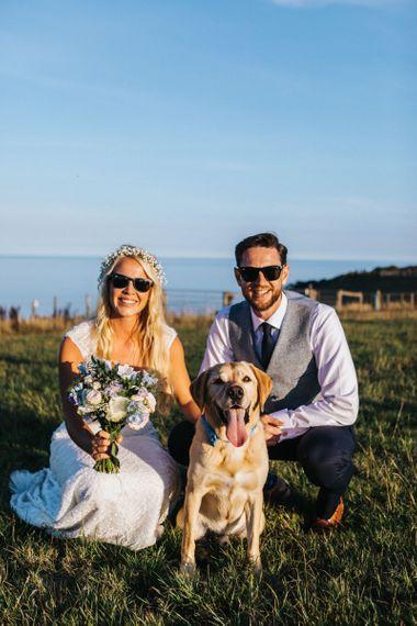 Bride in Sophia Tolli Wedding Dress and Groom in Grey Waistcoat Posing with Their Pet Dog