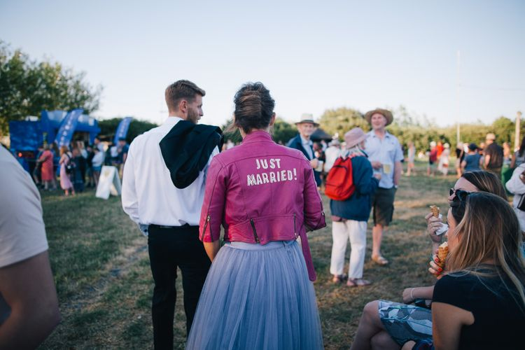 Bride In Customised Pink Leather Jacket // Authentic Festival Weddings At In The Wyldes Wedding Venue Site With Stage, Bar And Camping Area For Ready-to-go Festival Wedding
