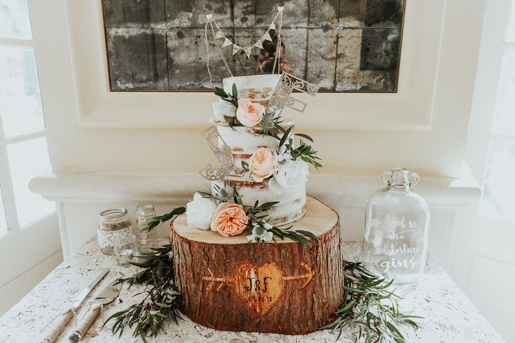 Semi Naked Wedding Cake on Tree Stump Cake Stand Decorated with Miniature Bunting Cake Topper and Flowers
