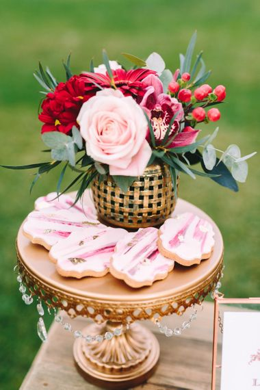 Pink Iced Wedding Biscuits and Floral Arrangement on Gold Cake Stand