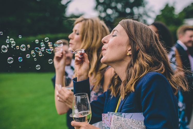Bubbles for Guests. A Quintessentially British Venue at Cambridge Cottage, Royal Botanic Gardens Kew. Bride Wears Paloma Blanca from Pure Couture Bridal and Groom Wears Tailored Suit from Hackett London.