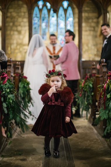 Flower girl in burgundy velvet dress and faux fur coverup