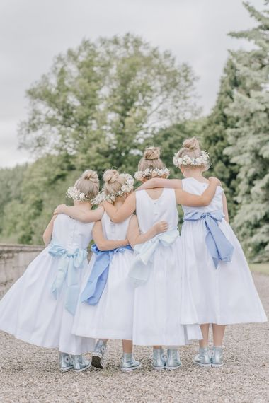 Traditional white dresses with blue sashes and converse trainers