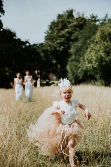 Little girl in peach tulle skirt and feather headdress