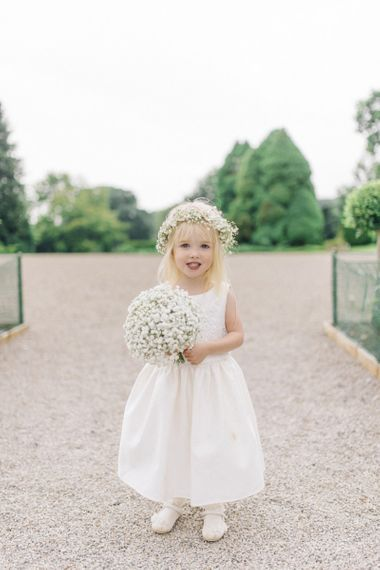 Flower girl in white dress with gypsophila bouquet and flower crown