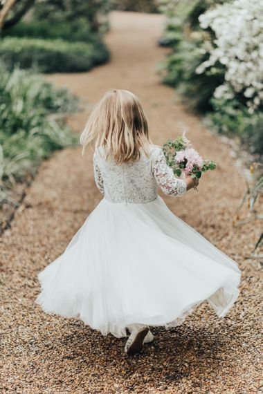 Flower girl in white dress twirling