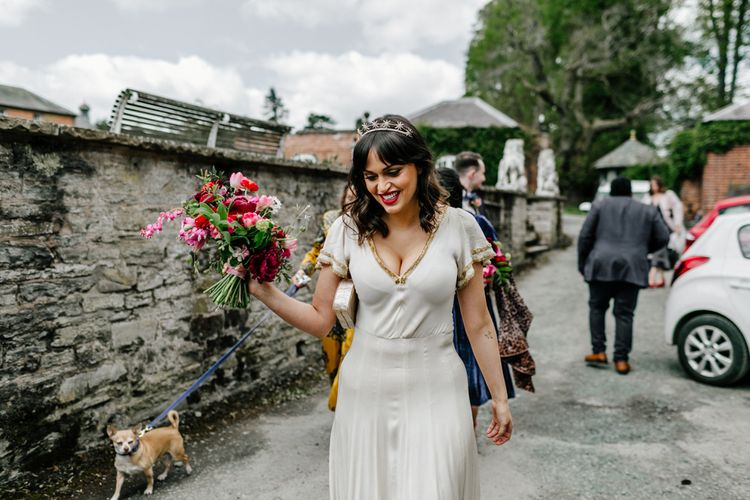 Beautiful Bride in Nude Vintage Wedding Dress with Gold Trims Wearing a Crown and Holding a Bright Wedding Bouquet