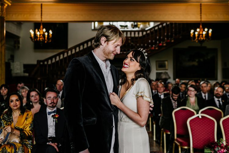 Wedding Ceremony at Walcot Hall with Happy Bride in Vintage  Wedding Dress with Gold Trims and Groom in Velvet Blazer Embracing