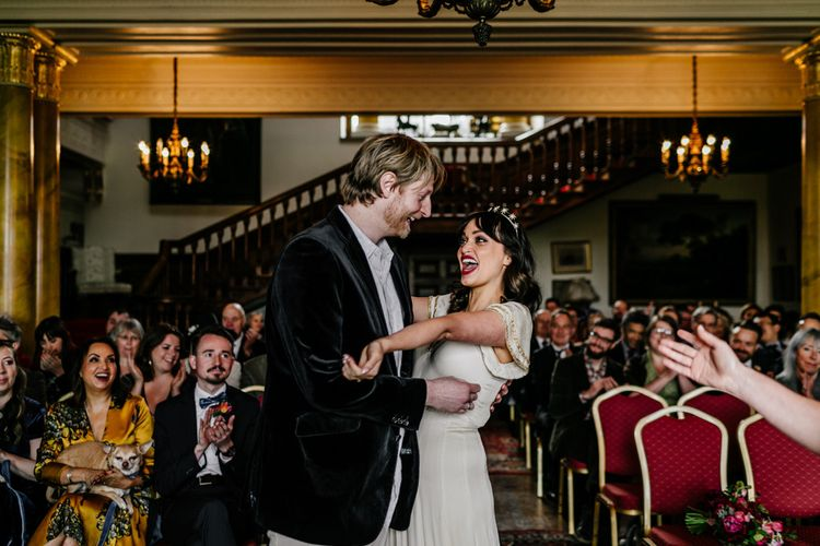 Wedding Ceremony at Walcot Hall with Bride in Vintage  Wedding Dress with Gold Trims and Groom in Velvet Blazer Laughing