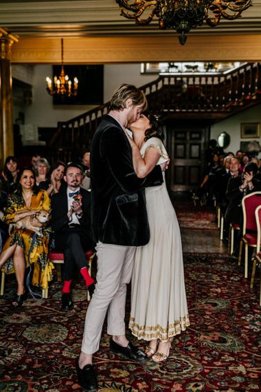 Wedding Ceremony at Walcot Hall with Bride in Vintage  Wedding Dress with Gold Trims and Groom in Velvet Blazer Kissing