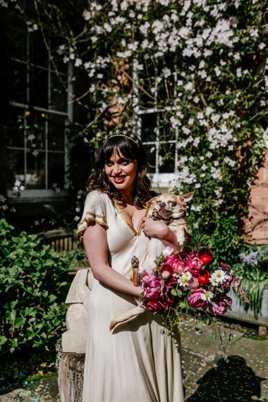 RockNRoll Bride in Vintage Wedding Dress with Gold Trim Holding Her Pet Dog