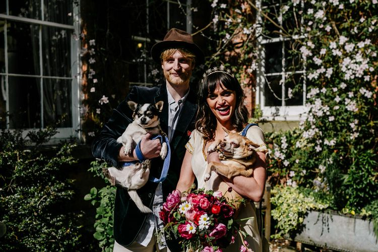 Stylish Bride and Groom Holding Their Pet Dogs