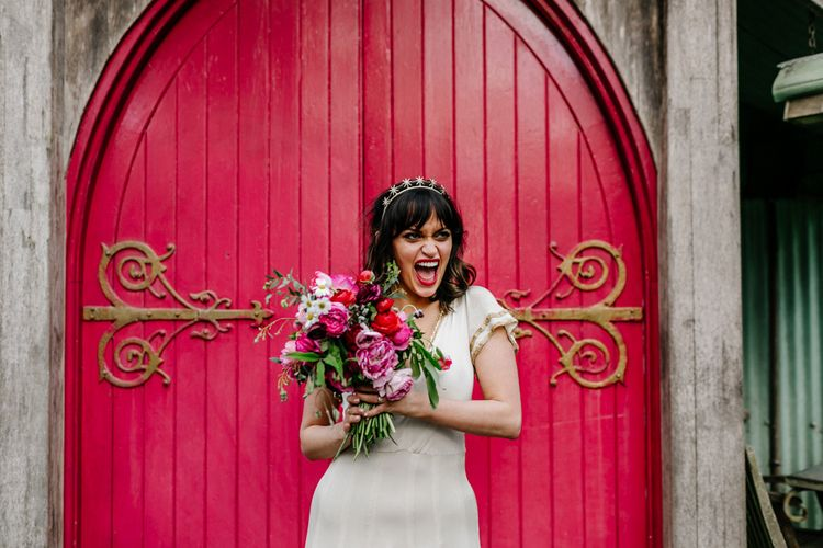 Happy Bride in Vintage Wedding Dress with Batwing Sleeves Holding a Red and Pink Floral Bouquet