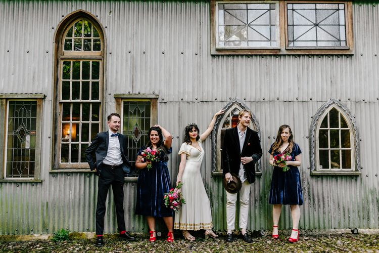 Stylish Wedding Party with Bridesmaids in Navy Velvet Dresses and Red Shoes, Bride in Vintage Wedding Dress and Groomsmen in Trousers and Blazers