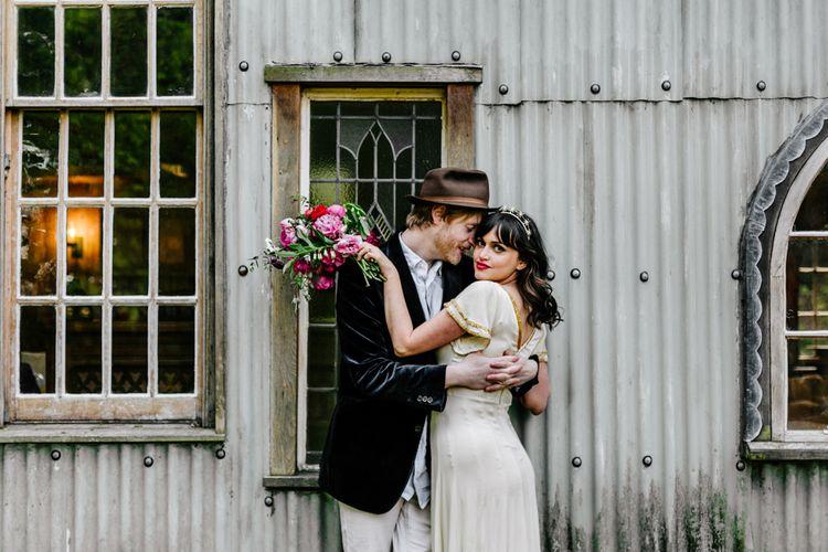Groom in Navy Velvet Blazer and Hat Hugging His Beautiful Bride in Vintage Wedding Dress with Gold Trim-110
