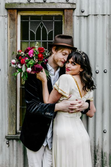 Bride in Vintage Wedding Dress with Gold Trim and Groom in Navy Velvet Blazer and Hat Embracing