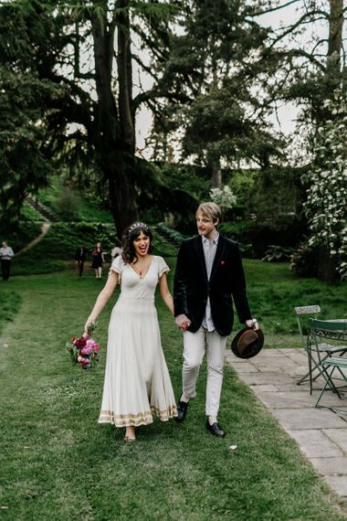 Bride in Vintage Wedding Dress with Gold Trim and Groom in Navy Velvet Blazer and Hat Waking Hand in Hand-114