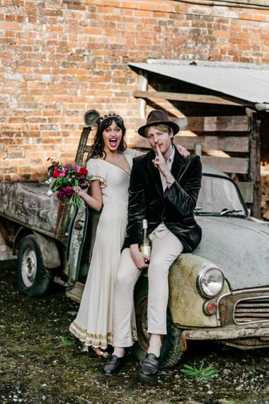 Bride in Vintage Wedding Dress with Gold Trim and Groom in Navy Velvet Blazer and Hat Sitting on an Old Truck-115