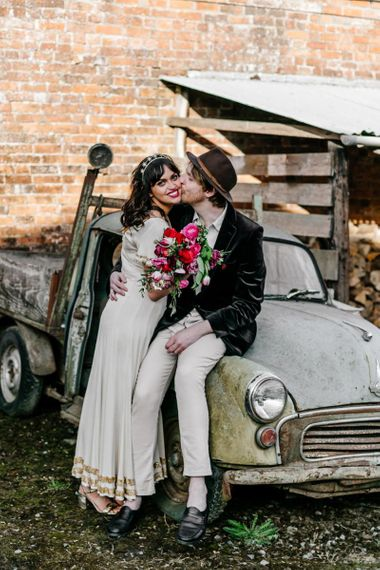 Bride in Vintage Wedding Dress with Gold Trim and Groom in Navy Velvet Blazer and Hat Sitting on an Old Truck Kissing