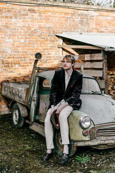 Groom in Navy Velvet Blazer and Hat Sitting on an Old Truck