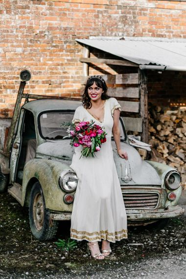 Bride in Vintage Wedding Dress with Gold Trim Holding a Red and Pink Wedding Bouquet Sitting on an Old Truck