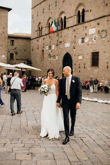 Bride wears Justin Alexander wedding dress with white flower bouquet