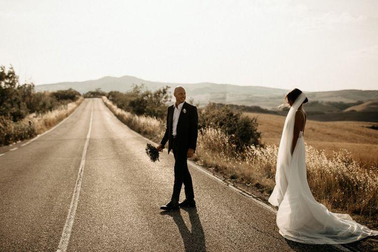 Bride wears Justin Alexander wedding dress with groom in black suit