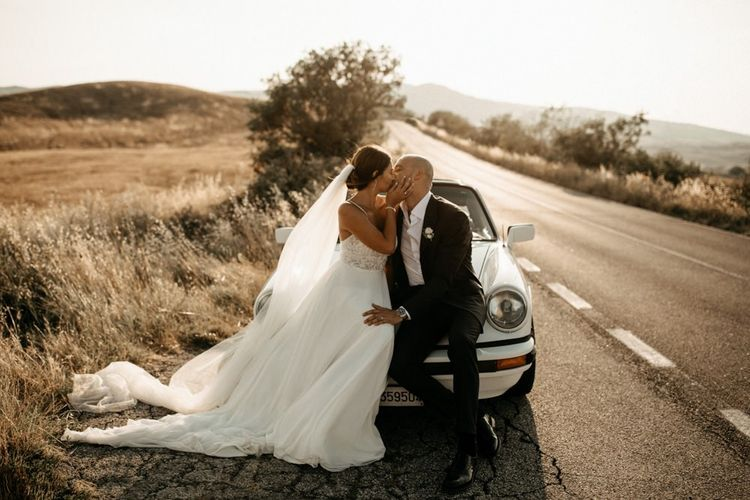 Bride wears Justin Alexander wedding dress with groom in black suit and white wedding car