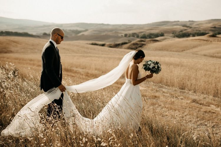 Justin Alexander wedding dress with long veil and groom in black suit