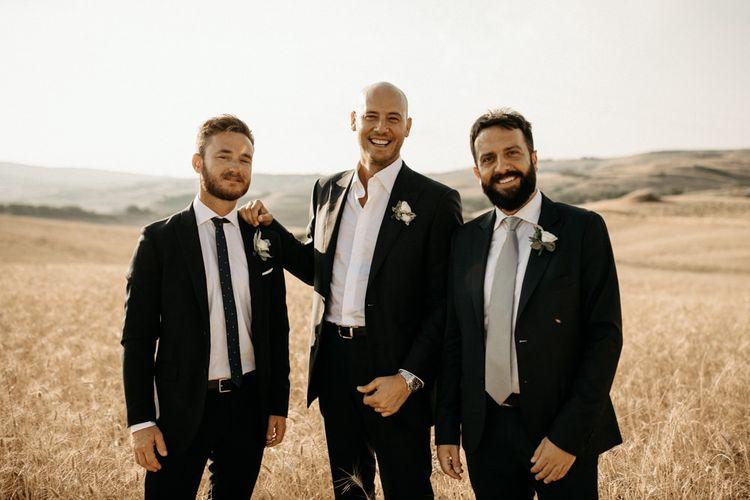 Groom and groomsmen in black wedding suits
