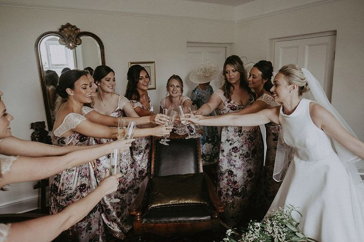 Bride in Suzanne Neville wedding dress toasts with bridesmaids