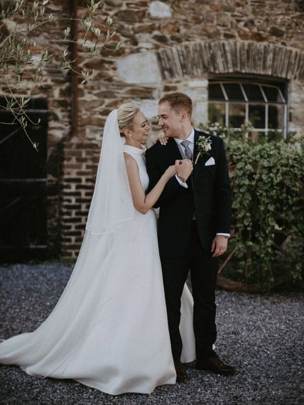 Bride wearing Suzanne Neville wedding dress with groom