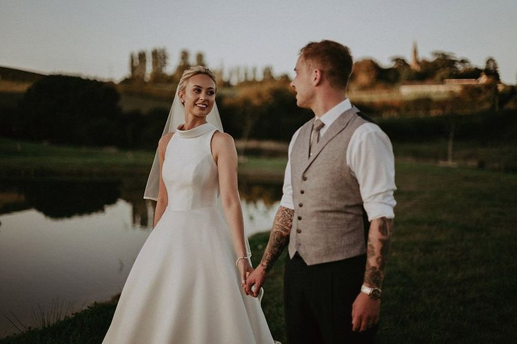 Bride wearing Suzanne Neville wedding dress with groom in waistcoat