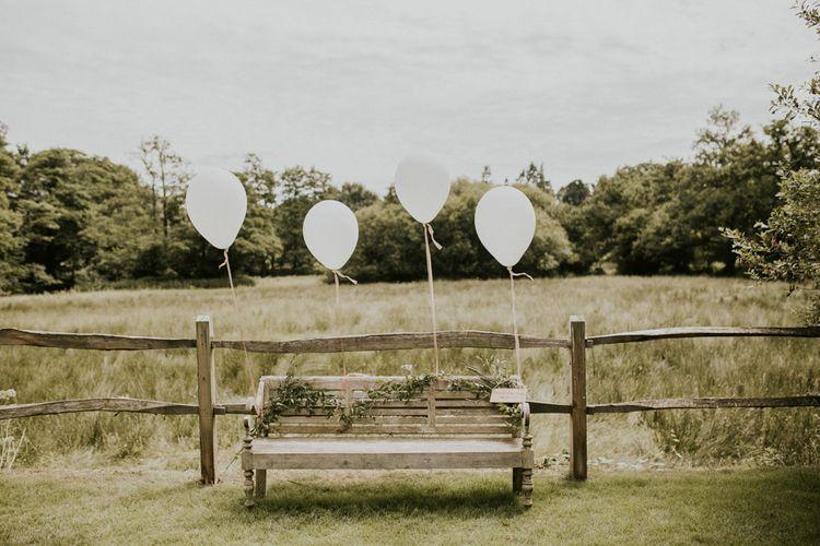 Wooden Bench with Giant Balloon Decor & Greenery Garland | Millbridge Court, Surrey Wedding with DIY Decor, Foliage & Giant Balloons | Nataly J Photography