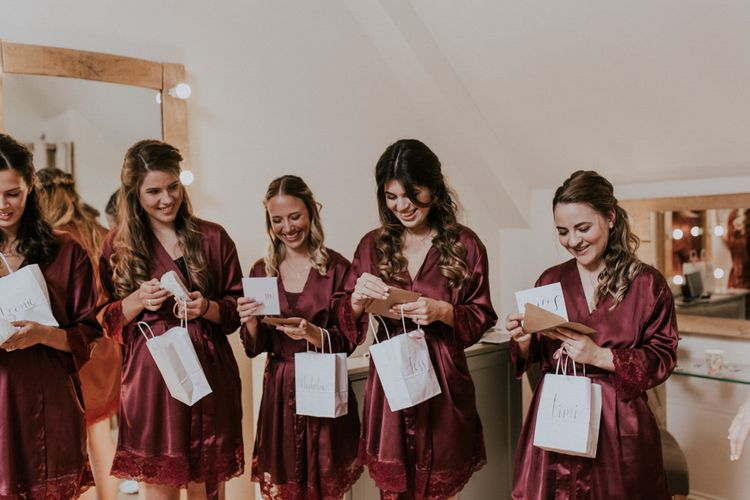 Bridesmaids in Matching burgundy Robes Opening Their Bridesmaid Gift Bags | Millbridge Court, Surrey Wedding with DIY Decor, Foliage & Giant Balloons | Nataly J Photography