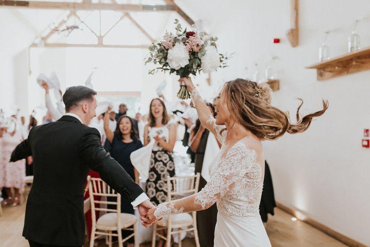 Bride & Groom Wedding Breakfast Entrance | Bride in Madison James Bridal Gown | Groom in Tuxedo | Millbridge Court, Surrey Wedding with DIY Decor, Foliage & Giant Balloons | Nataly J Photography